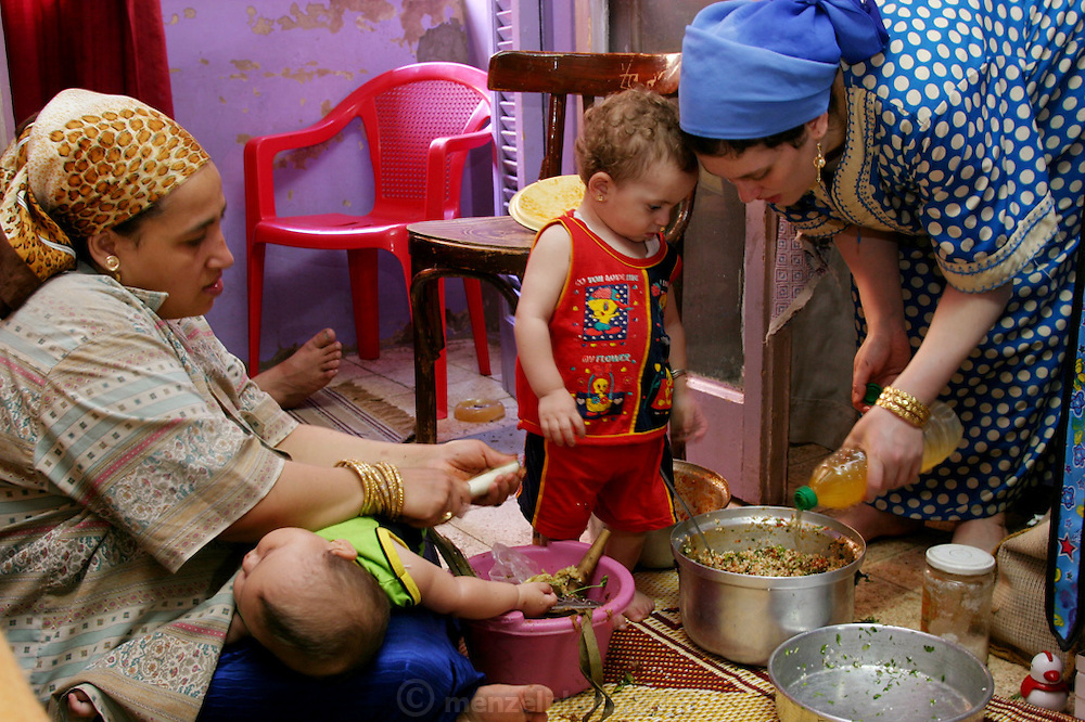 (MODEL RELEASED IMAGE). Nadia Ahmed (left) and her sister-in-law Abadeer make mahshi (stuffed food, in this case small eggplants) on the floor of Nadia's fourth-floor apartment. Heedless of the activity, baby Nancy sleeps on Nadia's lap; meanwhile, Abadeer's daughter Israa restlessly patrols the space. (Supporting image from the project Hungry Planet: What the World Eats.) The Ahmed family of Cairo, Egypt, is one of the thirty families featured, with a weeks' worth of food, in the book Hungry Planet: What the World Eats.