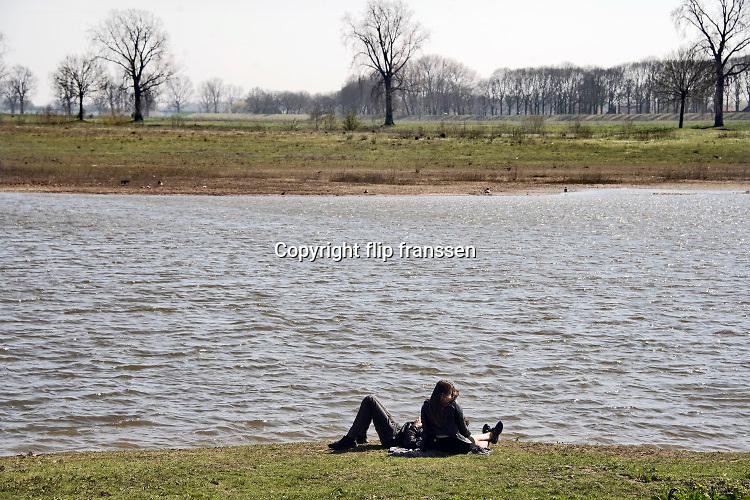 Nederland, Batenburg, 5-4-2020 Een jong stel, stelletje, zit aan de oever van de Maas tijdens de coronacrisis . Mensen moeten ook met het mooie weer zoveel mogelijk thuis of binnen blijven . Het is lekker voorjaarsweer . Er zijn niet veel mensen in dit natuurgebied, de Liendense waard . De uiterwaarden van de Maas bij het stadje zijn heringericht. Er is onder meer een nevengeul aangelegd waardoor er geregeld water door het gebied stroomt. De uiterwaarden ontwikkelen zich hierdoor tot een interessant natuurgebied. Het is een project ihkv ruimte voor de rivier ., de meanderende maas om in tijden van hoogwater een betere afvoer te hebben. Foto: Flip Franssen