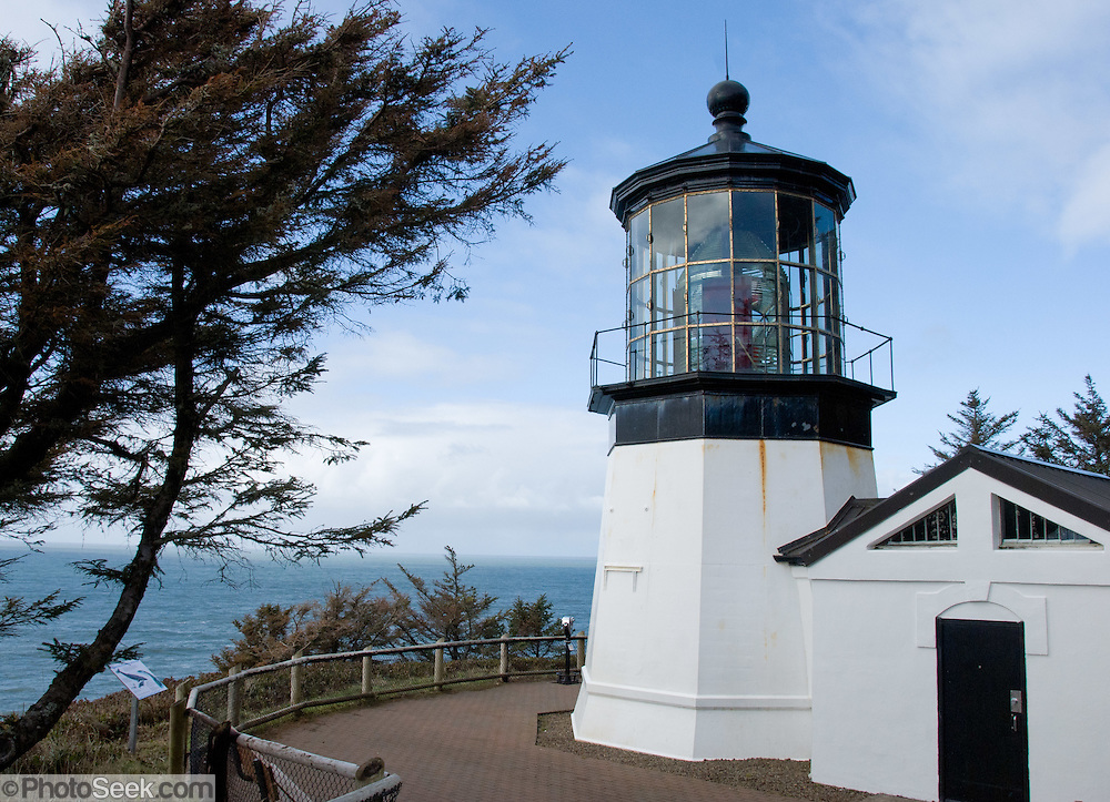 """Cape Meares State Scenic Viewpoint on the Oregon coast, USA. Cape Meares Lighthouse was commissioned in 1890 and decommissioned in 1963.  The tower stands 38 feet high and is the shortest lighthouse in Oregon. The lighthouse's first order Fresnel lens (pronounced """"Fraynel"""") was made in Paris, France, shipped around South America's Cape Horn to Cape Meares and then hauled 217 feet up the cliff for installation."""