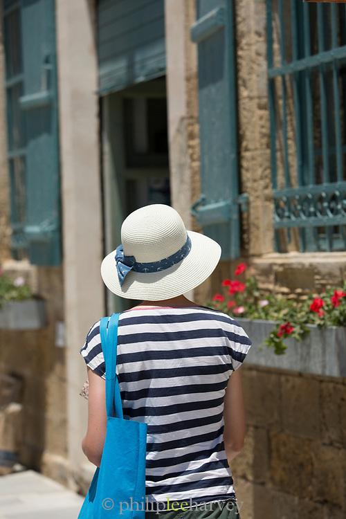 Female tourist walking on sidewalk, Paphos, Cyprus