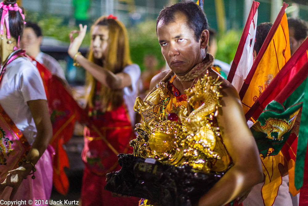 01 OCTOBER 2014 - BANGKOK, THAILAND: A firewalker goes into a trance before running through the fire pit at Wat Yannawa (also spelled Yan Nawa) during the Vegetarian Festival in Bangkok. The Vegetarian Festival is celebrated throughout Thailand. It is the Thai version of the The Nine Emperor Gods Festival, a nine-day Taoist celebration beginning on the eve of 9th lunar month of the Chinese calendar. During a period of nine days, those who are participating in the festival dress all in white and abstain from eating meat, poultry, seafood, and dairy products. Vendors and proprietors of restaurants indicate that vegetarian food is for sale by putting a yellow flag out with Thai characters for meatless written on it in red.     PHOTO BY JACK KURTZ