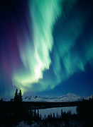 Whitish-green and reddish-purple aurora at dusk on March 23, 2002, frozen Chulitna River with Mt. McKinley and the Alaska Range beyond, Denali State Park and Denali National Park, Alaska.