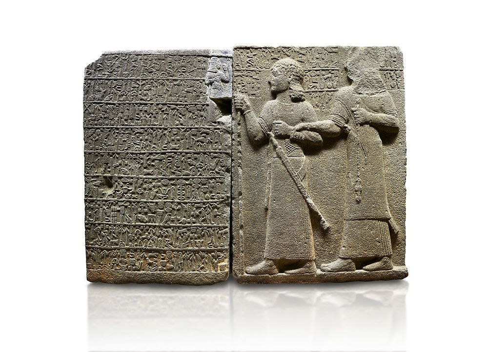 """Hittite monumental relief sculpted orthostat stone panel of Royal Buttress. Basalt, Karkamıs, (Kargamıs), Carchemish (Karkemish), 900-700 B.C. Anatolian Civilisations Museum, Ankara, Turkey.<br /> <br /> Hieroglyph panel (left) - Discourse of Yariris. Yariris presents his predecessor, the eldest son Kamanis, to his people. <br /> Right Panel - King Araras holds his son Kamanis from the wrist. King carries a sceptre in his hand and a sword at his waist while the prince leans on a stick and carries a sword on his shoulder. <br /> <br /> Hieroglyphs reads; """"This is Kamanis and his siblings.) held his hand and despite the fact that he is a child, I located him on the temple. This is Yariris' image"""".  <br /> <br /> Against a white background. .<br />  <br /> If you prefer to buy from our ALAMY STOCK LIBRARY page at https://www.alamy.com/portfolio/paul-williams-funkystock/hittite-art-antiquities.html  - Type  Karkamıs in LOWER SEARCH WITHIN GALLERY box. Refine search by adding background colour, place, museum etc<br /> <br /> Visit our HITTITE PHOTO COLLECTIONS for more photos to download or buy as wall art prints https://funkystock.photoshelter.com/gallery-collection/The-Hittites-Art-Artefacts-Antiquities-Historic-Sites-Pictures-Images-of/C0000NUBSMhSc3Oo ."""