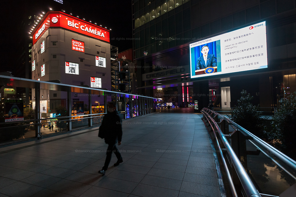 Japanese Prime Minister, Yoshiihide Suga  a large TV screen in Akihabara UDX building reporting the news that he is considering  declaring a state of Emergency in the Greater Tokyo area to combat rising COVID-19 infection rates. Akihabara, Tokyo, Japan. Monday January 4th 2021. In response to a apparent second-wave of COVID-19 infections and after calls to act by Tokyo Governor, Yuriko Koike, PM Suga stated that he is prepared to impose a state of emergency,, similar to the one called in Spring 2020, advising businesses to close or limit opening and urging people to avoid  going out.