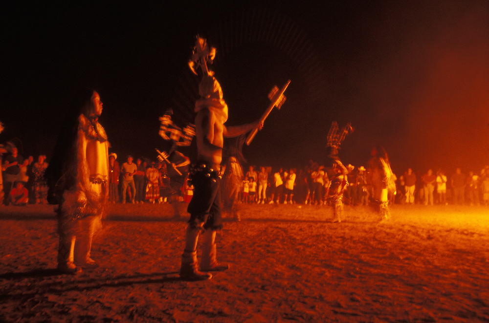 Mountain spirits dance together with Apache girls, all dressed in buckskin clothes, beside a big bonfire at night during a Sunrise Dance on the San Carlos Apache Indian Reservation in Arizona, USA. The clown, in white hood, swings a bull-roarer in the air. The Sunrise Dance, a first menstruation rite, is held during the summer, within one year after the girl has had her first menstruation, and lasts for four days. The ceremony is an enactment of the Apache creation myth and during the rites the girl 'becomes' Changing Woman, a mythical female figure, and comes into possession of her healing powers. The rites are supposed to prepare the girl for adulthood and to give her a long and healthy life without material wants.