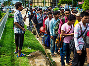 05 JULY 2017 - POIPET, CAMBODIA: A blind Cambodian musician performs for tips in front of a group of Cambodian migrant workers going to Thailand. The Thai government proposed new rules for foreign workers recently. The new rules include fines of between 400,000 and 800,00 Thai Baht ($12,000 - $24,000 US) and jail sentences of up to five years for illegal workers and people who hire illegal workers. Hundreds of companies fired their Cambodian and Burmese workers and tens of thousands of workers left Thailand to return to their countries of origin. Employers and human rights activists complained about the severity of the punishment and sudden implementation of the rules. On Tuesday, 4 July, the Thai government suspended the new rules for 180 days and the Cambodian and Myanmar governments urged their citizens to stay in Thailand, but the exodus of workers continued through Wednesday.     PHOTO BY JACK KURTZ
