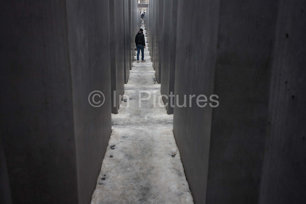 The field of stelae of the outdoor Holocaust Memorial, a reminder of Jewish persecution and anti-Semitism in Europe during the second world war. U.S. architect Peter Eisenman's controversial design was chosen as a fitting tribute to the Jews that died before and during World War II as part of Hitler's plan to exterminate them. Eisenman's design is quite unique and has drawn both praise and criticism. Occupying about 205,000 square feet (19,000 square meters) of space near the Brandenburg Gate and just a short distance from where the ruins of Hitler's bunker is buried, the Berlin Holocaust Memorial is made up of 2,711 gray stone slabs that bear no markings, such as names or dates. It is estimated that the Nazis used these camps to kill an estimated 11 million people.