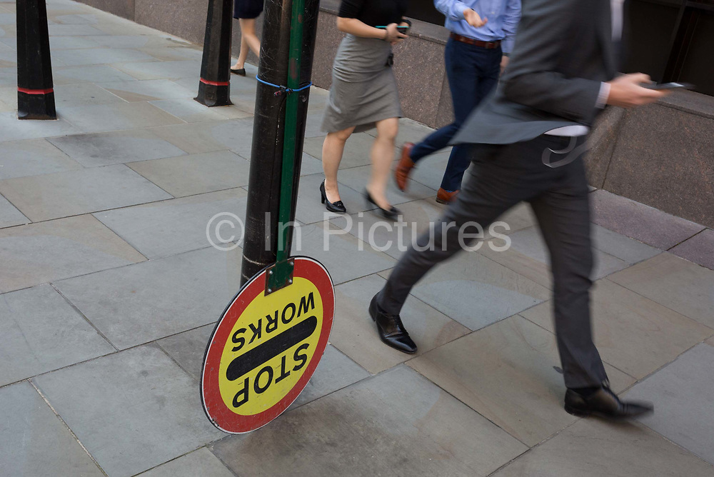 City workers walk past an upside down building site Banksmans lollipop sign that usually tells road-users to allow for turning construction traffic, on Sun Street near Liverpool Street Station in the City of London, the capitals financial district - aka the Square Mile, on 8th August, in London, England.