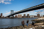 A man takes a photograph from Main Street Park, under the Manhattan Bridge across the East River towards Manhattan from Dumbo, Brooklyn, New York City, United States of America.