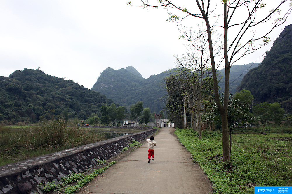 A young boy runs down a lane on Cat Ba Island, the largest island in Ha Long Bay, Vietnam. The bay consists of a dense cluster of 1,969 limestone monolithic islands. Ha Long Bay, is a UNESCO World Heritage Site, and a popular tourist destination. Ha Long, Bay, Vietnam. 11th March 2012. Photo Tim Clayton