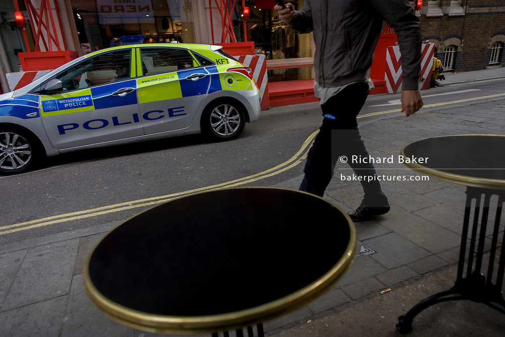 As a Met police car drives past, a young man walks past  cafe tables.