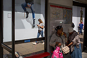 A shopper eats a banana in a bus stop near the legs of a fashion store hoarding, on 31st July 2017, in Oxford Street, London, England.