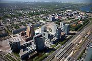 Nederland, Amsterdam, Zuideramstel, 12-05-2009; zicht op het financiele centrum van Amsterdam, de Zuidas, met de ringweg A10 en station Zuid/WTC (onder in beeld). Links het hoofdkantoor van ABN-AMRO met daar achter twee torens van het wooncomplex Gershwin. Langs de A10 het complex Mahler 4, in de verte de Vrije Universiteit met academisch zzikenhuis VU en het water van de Nieuwe Meer.<br /> Op het tweede plan de wijk Buitenveldert in de achtergrond. Er zijn plannen om snelweg en de spoorlijn te overkluizen of ondertunnelen en dit 'dokmodel' zou door een publiek private samenwerking gerealiseerd moeten worden. <br /> Swart collectie, luchtfoto (25 procent toeslag); Swart Collection, aerial photo (additional fee required)<br /> foto Siebe Swart / photo Siebe Swart