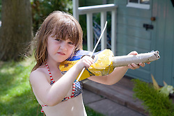 Little girl playing a homemade toy violin,