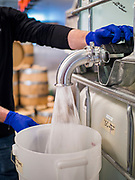 """20 MARCH 2020 - DES MOINES, IOWA: GREG BIAGI, the distiller at the Foundry, a Des Moines distiller, pours hand sanitizer into a 5 gallon jug. The distillery suspended its distilling operations to make hand sanitizer this week. They distributed it free to people who came to their building. On Friday thousands of people came to get some. There line was more than one mile long. On Friday morning, 20 March, Iowa reported 45 confirmed cases of the Coronavirus. Restaurants, bars, movie theaters, places that draw crowds are closed for at least 30 days. There are no """"shelter in place"""" orders in effect anywhere in Iowa but people are being encouraged to practice """"social distancing"""" and many businesses are requiring or encouraging employees to telecommute.       PHOTO BY JACK KURTZ"""