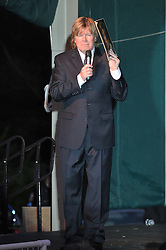 Peter Noone holding his old album cover photo while performing at the Hamden Free Summer Concert Series July 2009.