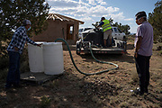 Water Warrior CB Barton fills water barrels for Isaiah Tsosie and Ryland Jim who are building a hogan. Volunteers with Water Warriors deliver water to families in remote parts Coyote Canyon Chapter in the Navajo, Nation near Gallup, New Mexico.