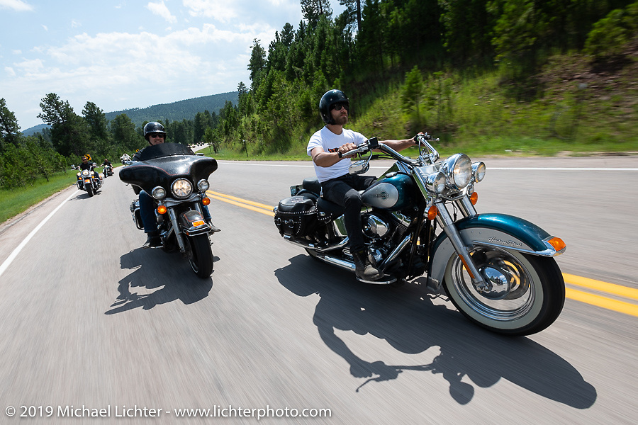 Lance Knight on his 1996 HD Bad Boy with his Dad Timothy behind him on his 1995 HD Electra Glide on the Cycle Source ride down Vanocker Canyon back from Nemo to the Iron Horst Saloon during the Sturgis Black Hills Motorcycle Rally. SD, USA. Wednesday, August 7, 2019. Photography ©2019 Michael Lichter.
