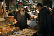A fishmonger serves a customer at his stall in the Athens Central Market on Athinas Street. Athens, Greece