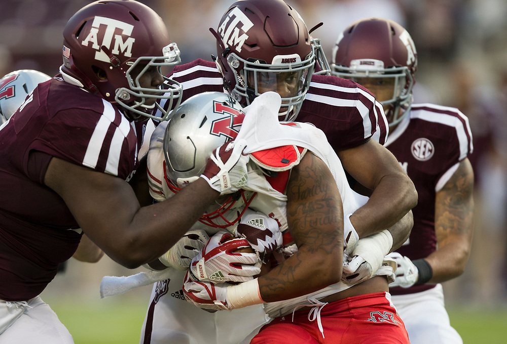 Nicholls State running back Kyran Irvin (30) is stopped for  loss by Texas A&M defensive lineman Daylon Mack (5) and lineman Qualen Cunningham (9) during the second quarter of an NCAA college football game Saturday, Sept. 9, 2017, in College Station, Texas. (AP Photo/Sam Craft)
