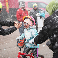 Kyler Atencio finishes the biking portion of the Quad Kids race, Saturday, Feb. 16 in Grants during the Mt. Taylor Winter Quadrathlon as volunteer Maria Magana wipes snow from her glasses before she begins her run.