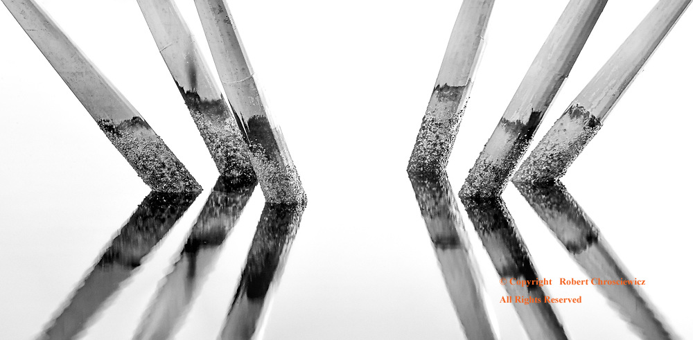 Divergent Pylons (B&W): A bridges pylons are reflected in the still waters of False Creek, Vancouver British Columbia Canada.