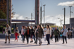 © Licensed to London News Pictures . 24/09/2014 . Media City , Salford , UK . Commuters emerge from a tram . Autumn sunshine and big reflected light off the surface of glass buildings at Salford's Media City this morning as commuters travel to work  . Photo credit : Joel Goodman/LNP