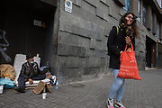 A young woman has delivered some food to a man of Romanian origin who has settled in a central street in the city center after the decree of the state of alarm due to COVID19 crisis. He and his wife have been trapped in the city of Barcelona, with some bus tickets to Romania, which they could not use because the borders were closed after. Barcelona, 27th march. Barcelona, March 27th. Photo by Eva Parey.<br /> <br /> Many people have been living in Barcelona for a while, sleeping on its streets, there are around 2,500 people, of different nationalities, ages and genders, but it is the quiet of the city - with hardly any passers-by -, in State of Alarm, that betrays their presence on the streets.<br /> The confinement order issued on March 15 cannot be applied to them. Their problem is twofold. Find a place to spend the day and avoid to be exposed to COVID disease19. Some have been able to occupy spaces in the city that before, being visible for the society, were prohibited. Others would like to occupy any of the places in the social shelters that the Barcelona City Council has specifically opened for them. More than fear of  the disease, there are other fears. Loss of freedom seems the most precious asset for those who do not want to confine themselves in a closed space, in addition to protecting themselves from possible thefts or conflicts of all kinds. Behind each face there is a story. Some have been with this way of life for some time, but others, the cessation of many jobs or the closing of borders, have left them trapped in the street with no other option.