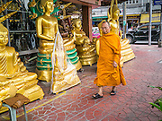 """12 NOVEMBER 2012 - BANGKOK, THAILAND:   A monk passes a shop on Bamrung Muang Street in Bangkok. Thanon Bamrung Muang (Thanon is Thai for Road or Street) is Bangkok's """"Street of Many Buddhas."""" Like many ancient cities, Bangkok was once a city of artisan's neighborhoods and Bamrung Muang Road, near Bangkok's present day city hall, was once the street where all the country's Buddha statues were made. Now they made in factories on the edge of Bangkok, but Bamrung Muang Road is still where the statues are sold. Once an elephant trail, it was one of the first streets paved in Bangkok. It is the largest center of Buddhist supplies in Thailand. Not just statues but also monk's robes, candles, alms bowls, and pre-configured alms baskets are for sale along both sides of the street.    PHOTO BY JACK KURTZ"""