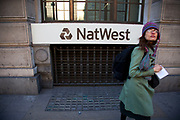Woman walks past a sign for Nat West Bank in the City of London. National Westminster Bank Plc, commonly known as NatWest, is the largest retail and commercial bank in the United Kingdom and has been part of The Royal Bank of Scotland Group Plc since 2000.