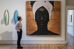"© Licensed to London News Pictures. 08/10/2020. LONDON, UK. A staff member views ""Novas Linguagens Do Mundo"", 2019, by Alexis Peskine.  Preview of 1-54 Contemporary African Art Fair, the leading international art fair dedicated to contemporary art from Africa and its diaspora, taking place at Somerset House.  The fair showcases the work of more than 110 emerging and established artists from Africa and is the only physical art fair taking place during Frieze Week.  Photo credit: Stephen Chung/LNP"