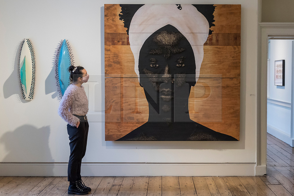 """© Licensed to London News Pictures. 08/10/2020. LONDON, UK. A staff member views """"Novas Linguagens Do Mundo"""", 2019, by Alexis Peskine.  Preview of 1-54 Contemporary African Art Fair, the leading international art fair dedicated to contemporary art from Africa and its diaspora, taking place at Somerset House.  The fair showcases the work of more than 110 emerging and established artists from Africa and is the only physical art fair taking place during Frieze Week.  Photo credit: Stephen Chung/LNP"""