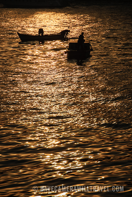 Two small fishing boats are silhouetted against the reflection of the setting sun on the Bosphorus in Istanbul, Turkey.