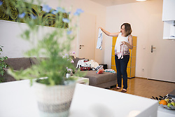 Pregnant woman standing in living room and looking at baby clothes, Munich, Bavaria, Germany