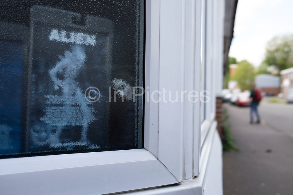 Alien in the window of a tattoo parlour in the inner city area of Northfiled, Birmingham under Coronavirus lockdown on 30th April 2020 in Birmingham, England, United Kingdom. Coronavirus or Covid-19 is a new respiratory illness that has not previously been seen in humans. While much or Europe has been placed into lockdown, the UK government has put in place more stringent rules as part of their long term strategy, and in particular social distancing.