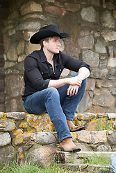 hot cowboy sitting on stone steps on a ranch