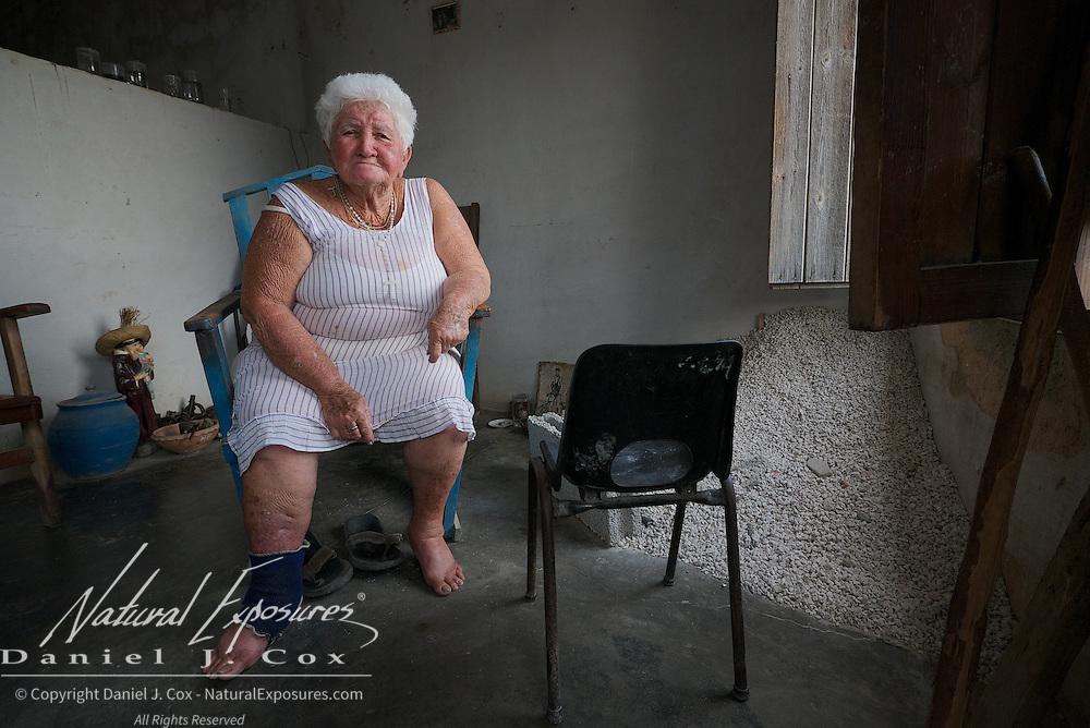 A very sad, older lady sits by her door in Trinidad, Cuba.