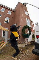 Belknap Mill President Peter Ellis (right) watches as Jake Hutchins and Matt Giuffrida of Hutchins Electric hoist a wreath donated by Opechee Garden Club to hang on the Belknap Mill Wednesday afternoon.   (Karen Bobotas/for the Laconia Daily Sun)