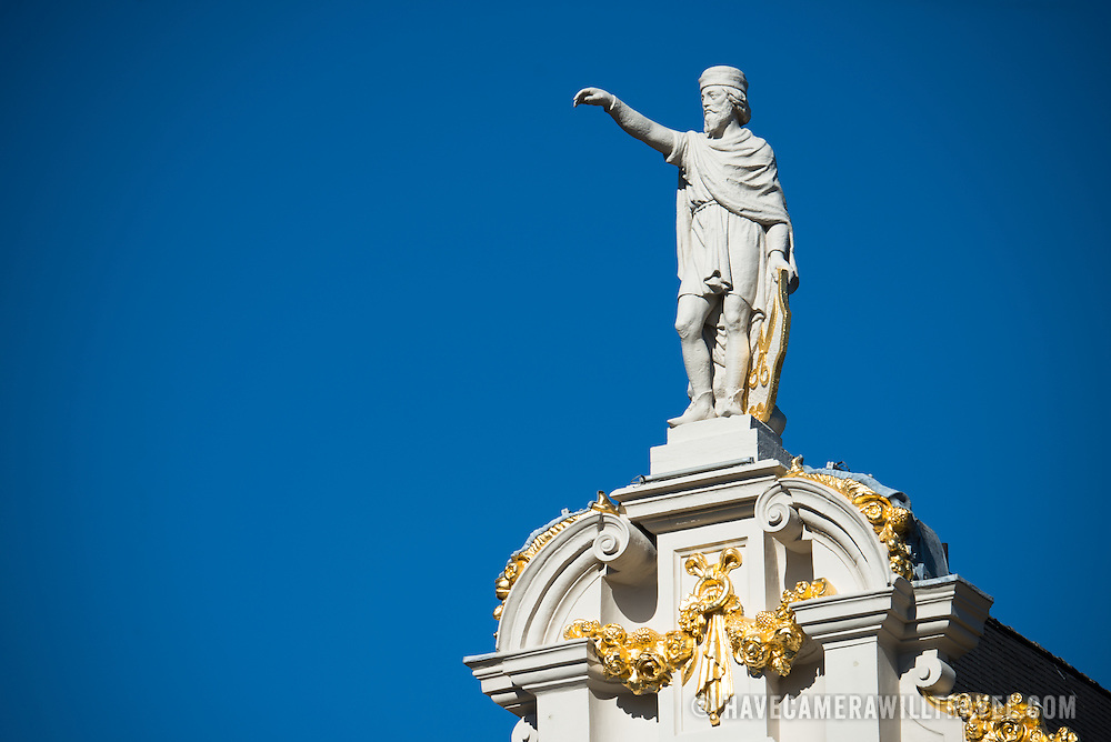 A statue standing on top of one of the hisotric buildings on Grand Place (La Grand-Place), a UNESCO World Heritage Site in central Brussels, Belgium. Lined with ornate, historic buildings, the cobblestone square is the primary tourist attraction in Brussels.