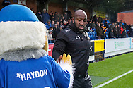 Doncaster Rovers manager Darren Moore touching/ slapping hands with Haydon the Womble during the The FA Cup match between AFC Wimbledon and Doncaster Rovers at the Cherry Red Records Stadium, Kingston, England on 9 November 2019.