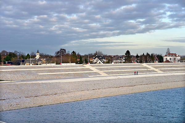 Nederland, Nijmegen, 10-12-2015 De bijna 4 km. lange nevengeul aan de overkant van de Waal bij Lent. Grootste onderdeel van de vele werken van Rijkswaterstaat om bij hoogwater een betere waterafvoer in de rivier te hebben. In precies drie jaar is het werk uitgevoerd. Het is een omvangrijk project waarbij onder meer de pijlers van het spoorviaduct een bredere basis kregen omdat die straks in de loop van het water staan. De Waalbrug heeft een verlenging via een nieuwe brug met drie gracieuze pijlers. Het dorp veurlent komt op een kunstmatig eiland te liggen met twee kleinere bruggen als ontsluiting. Een voetgangersbrug naar het recreatiegebied en een andere, de Promenadebrug, voor normaal verkeer. Ruimte voor de rivier, water, waal. In de nieuwe dijk wordt een drempel gebouwd die stapsgewijs water doorlaat en bij hoogwater overloopt. The Netherlands, Nijmegen Measures taken by Nijmegen to give the river Waal, Rhine, more space to flow during highwater and to prevent the risk of flooding. Room for the river. Reducing the level, waterlevel. Large project to create a new paralel gully, an extra flow of water, so the river can drain more water during highwater. Due to climate change and expected rise, increase of the sealevel, the Dutch continue to protect their land from the water. Foto: Flip Franssen/HH
