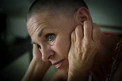 """Donna Branham poses in her home in Lenore, West Virginia after shaving her head on the steps of the West Virginia Capitol with a group of women in protest to mountaintop-removal mining. The shaving of their heads was symbolic of the mountains that have been stripped of all of the living things on them. It was also symbolic of the many people who are sick or dying as the result of Mountaintop Removal. Mountaintop Removal is a method of surface mining that literally removes the tops of mountains to get to the coal seams beneath. It is the most profitable mining technique available because it is performed quickly, cheaply and comes with hefty economic benefits for the mining companies, most of which are located out of state. It is the most profitable mining technique available because it is performed quickly, cheaply and comes with hefty economic benefits for the mining companies, most of which are located out of state. Many argue that they have brought wage-paying jobs and modern amenities to Appalachia, but others say they have only demolished an estimated 1.4 million acres of forested hills, buried an estimated 2,000 miles of streams, poisoned drinking water, and wiped whole towns from the map. """"People don't know how hard it is on the Appalachian people,"""" Branham said of mountaintop-removal mining. """"They have no idea. And they don't want to know. As long as they don't have to look at it, they can ignore it."""" © Ami Vitale"""