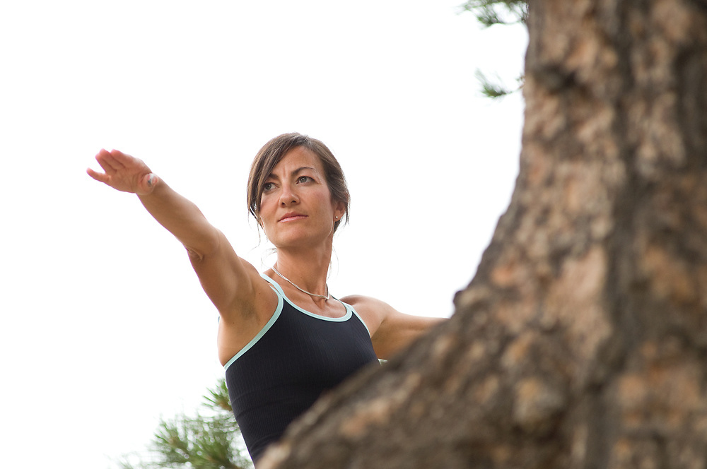 Woman doing warrior pose in the mountains by a tree