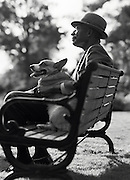 An elderly african-american man sits on a park bench with his dog on his lap.