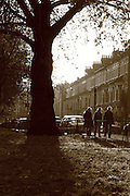 People walk along a street in Parsons Green in South-West in London on a sunny autumn afternoon