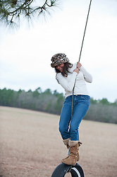 girl standing on a tire swing in Aiken, SC