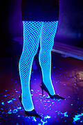 Woman wearing a skirt and glowing pantyhose standing on a concrete floor with scattered feathers.Black light