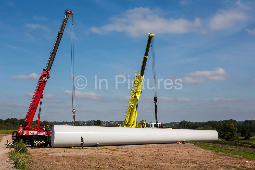Wind turbine installation. A workman secure the crane fixtures ready to lift the middle section of the new wind turbine at Alvington Court Farm before it is built. Forest of Dean. Gloucestershire.