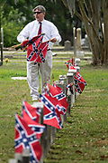 A confederate descendent collects battle flags from grave markers during Confederate Memorial Day at Magnolia Cemetery May 11, 2019 in Charleston, South Carolina. Confederate memorial day continues to be an official state holiday in South Carolina where the American Civil War began.