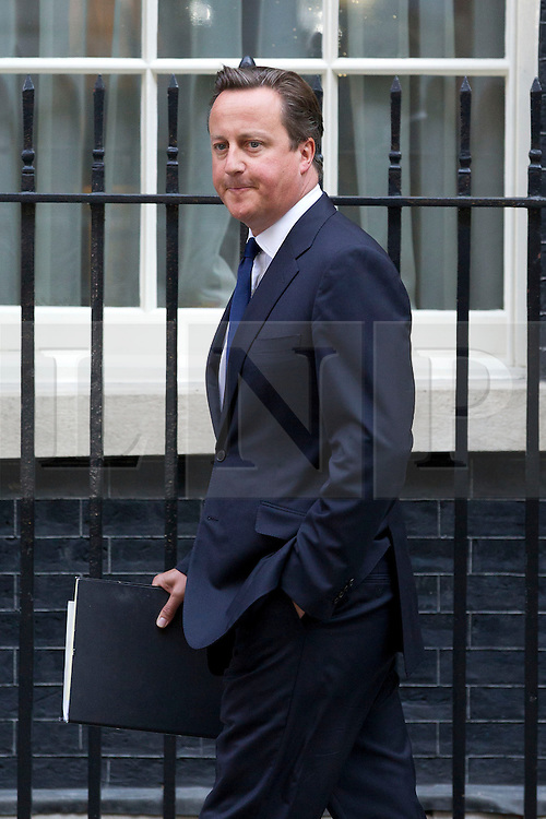 """© Licensed to London News Pictures. 29/08/2013. London, UK. David Cameron, the British Prime Minister, looks tense as he leaves a meeting of the his cabinet on Downing Street in London today (29/08/2013) as he heads for a recalled British Parliament preparing to debate the possibility of """"direct"""" military action over recent reports an alleged chemical weapons attack in Syria. Photo credit: Matt Cetti-Roberts/LNP"""